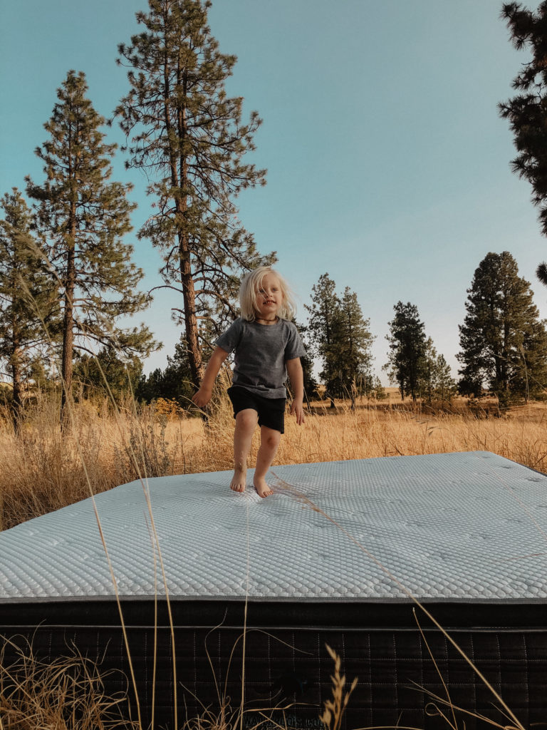 A young blonde boy jumps on a Wallaroo's Cool Mattress in a Wheat field.